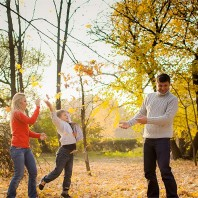 Famil of three throwing leaves