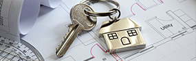 Plan with a key and a key ring of a house laid on top