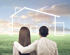 couple with arm around looking at a plan of a house with green fields behind
