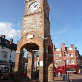 Chesham clock tower with shops behind in blue sky