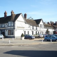 Saracens head pub in Beaconsfield Old Town with blue sky and cars parked outside
