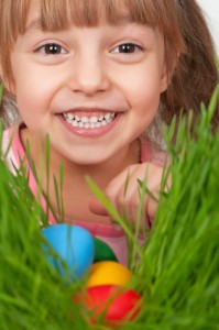 Little girl finds a multicoloured easter eggs in the tall green grass