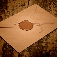 Sealed bid brown envelope with wax seal and string on wooden table