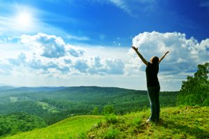 lady looking over hills and blue sky with arms open