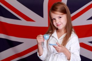 Lovely cheerful young girl holding a cup and saucer for English tea on background of the flag of Great Britain