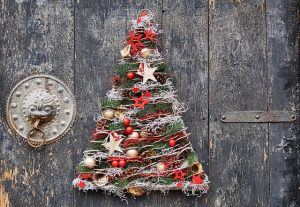 Christmas tree against a door with a round knocker